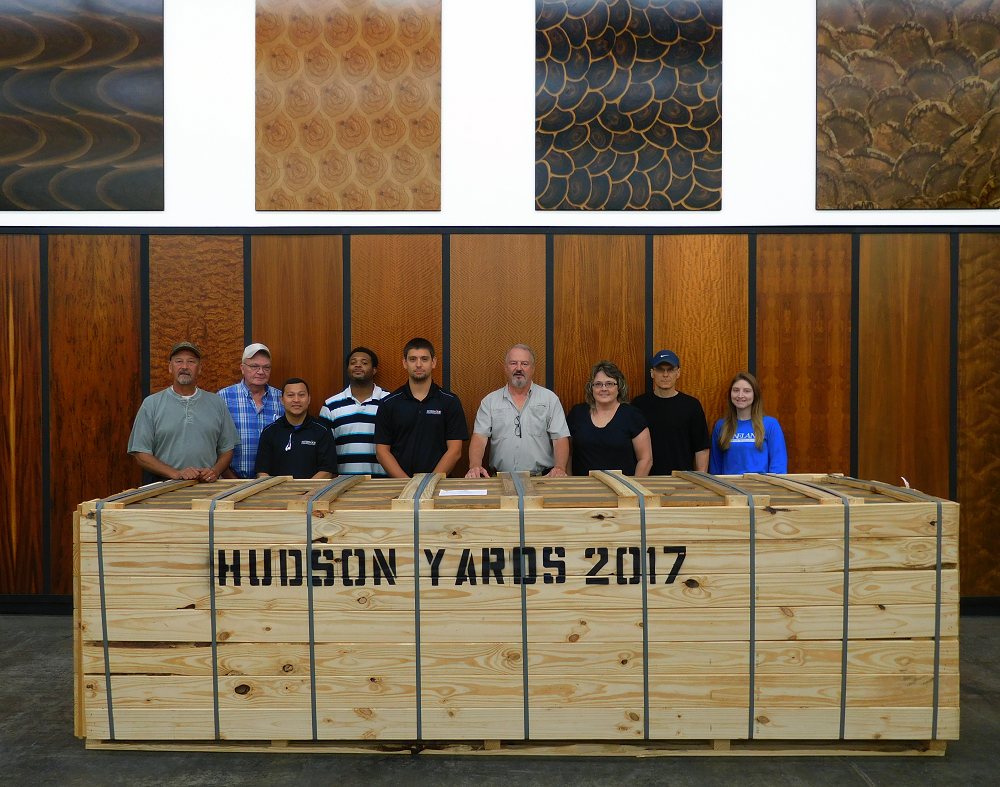 The whole Interwood team standing behind the pallet of Anegre veneer going into the 30 Hudson Yards building.