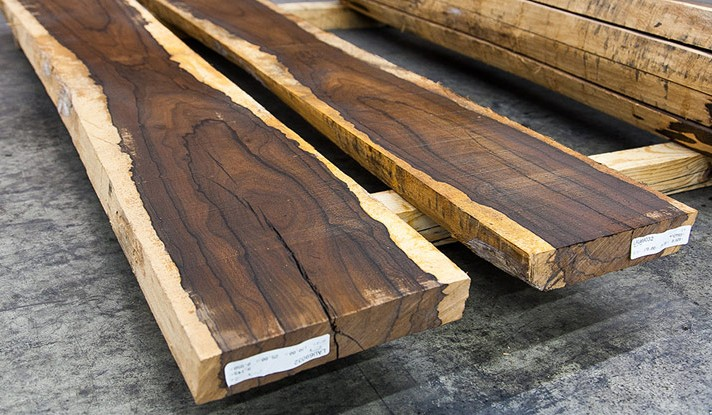Rosewood lumber with sap wood edges and cathedral growth structure.
